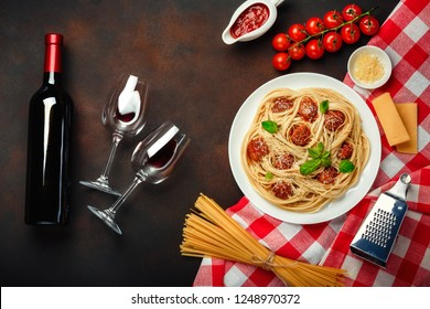 Spaghetti pasta with meatballs, cherry tomato sauce, cheese, wineglass and bottle on rusty background, top view.