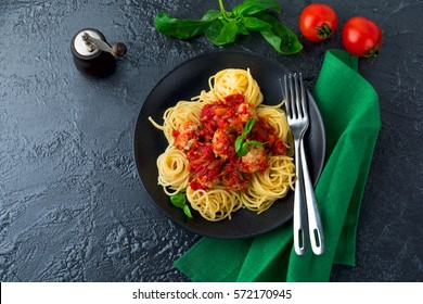Spaghetti pasta with meatballs, tomato sauce and basil on  dark background. Selective focus. Top view.