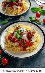 Spaghetti pasta meatballs with tomato sauce, basil, herbs parmesan cheese on dark background