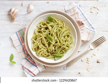 Spaghetti pasta with pesto sauce, basil, pine nuts and parmesan top view