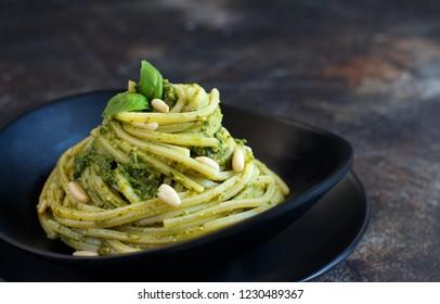 Spaghetti pasta with pesto sauce, basil, pine nuts and parmesan close up
