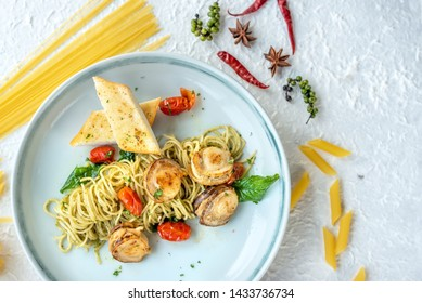 Spaghetti pasta Scallop and seafood in tomato sauce with pasta sauce, parsley in pan. sea food spaghetti in white dish on table.Plate of Italian spaghetti food is Spaghetti Scallop pesto clam.