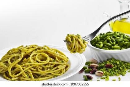 Spaghetti pasta seasoned with Homemade sicilian Pistachio pesto  with pistachio and extra vergin olive oil in the background