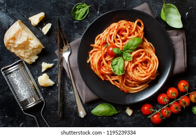 Spaghetti pasta with tomato sauce, basil and cheese on a dark table