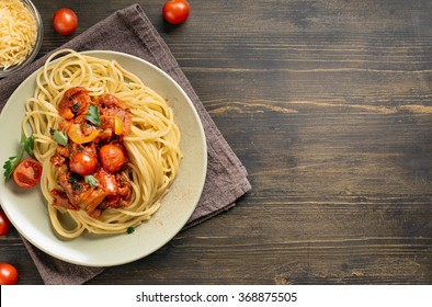 Spaghetti pasta with tomato sauce on wooden table. Top view with copy space.