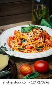 Spaghetti pasta with tomato sauce, parmesan and basil on a white plate. The classic tomato spaghetti: vegetarian tomato basil pasta. Old wooden background