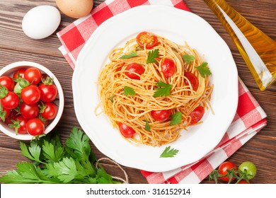 Spaghetti pasta with tomatoes and parsley on wooden table. Top view