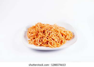 Spaghetti with pesto on a plate on a white background
