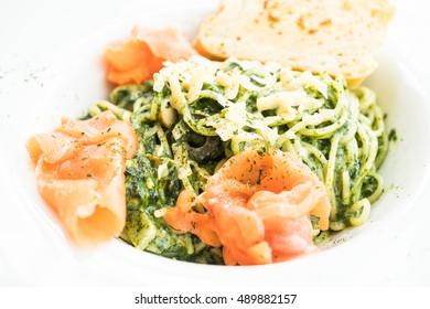 Spaghetti pesto with salmon meat in white plate