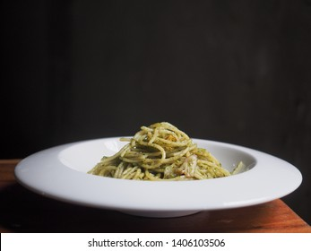 Spaghetti with pesto sauce in white plate on wooden table.