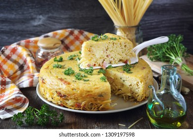 Spaghetti pie with lard and cheese, parsley dressing on dark background