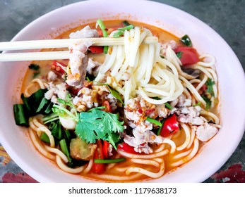 Spaghetti with pork spicy tomyum soup (Thai delicious food) on pink bowl fusion between italian food and  thailand street food.