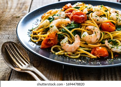 Spaghetti with prawns and vegetables on wooden background