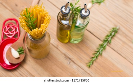 Spaghetti, Rosemary, oil and wooden spoon on wooden background with space for text