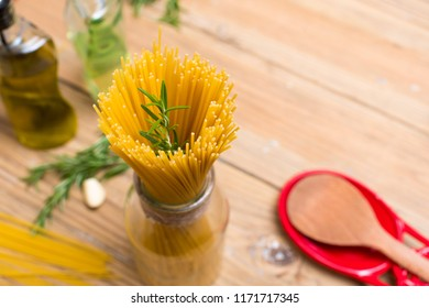 Spaghetti and rosemary on wooden background with space for text