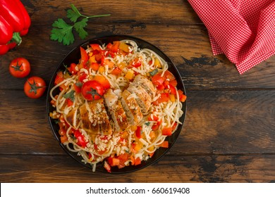 Spaghetti salad with fresh vegetables and baked chicken breast. Served on the black plate on the wooden rustic table, top view.