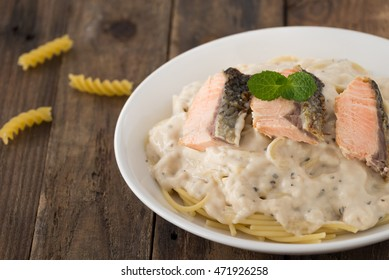 spaghetti with salmon on wood background