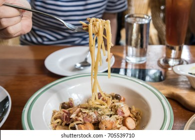 spaghetti with sausage  on a fork with woman, glass of water and coffee