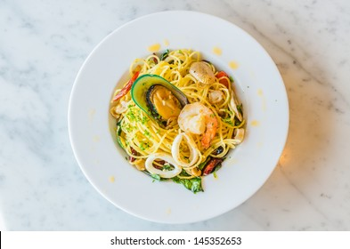 Spaghetti seafood in white dish on the stone table