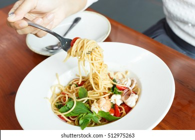 The spaghetti seafood white wine in white dish.close up hand woman eating spaghetti with fork.
