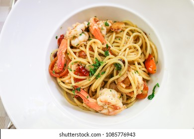 Spaghetti shrimp scampi with garlic,olive oil and chili on white plate. Top view