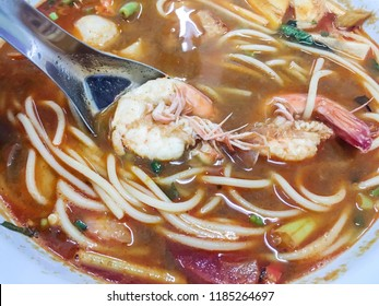 Spaghetti with shrimp spicy tomyum soup (Thai delicious food) on blue bowl fusion between italian food and  thailand street food.