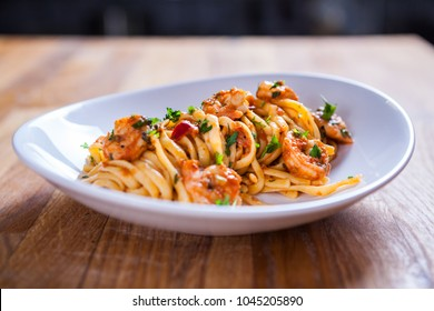 Spaghetti with shrimps, parsley and tomato sauce. Shrimps pasta on white plate. Seafood pasta on the wooden table in the kitchen. mediterranean  pasta. home made food
