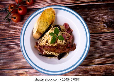Spaghetti with Spicy beef or pork in a dish on wood table. Spaghetti Spicy (Kie moa) Is a Thai style spaghetti. Roast Duck with egg noodles wanton soup fried ham with sweet sour spicy sauce.