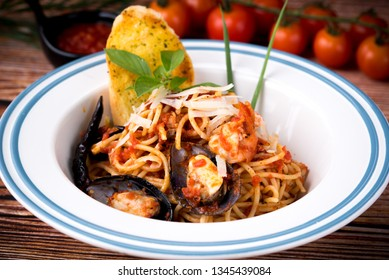 Spaghetti with Spicy Mixed Seafood in a dish on wood table. Spaghetti Spicy (Kie moa) Is a Thai style spaghetti. Roast Duck with egg noodles wanton soup fried fish with sweet sour spicy sauce.
