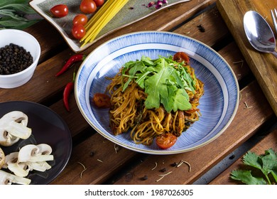 Spaghetti with Spicy Tune, Tomato Paste, Rocket Leaves and Lime Juice on Wood Table