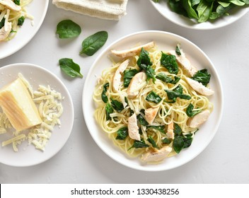 Spaghetti with spinach leaves, slices grilled chicken breast and grated cheese on white plate over stone background. Tasty pasta with vegetable leaves, healthy food. Top view, flat lay