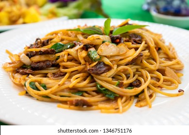 spaghetti stir fried spicy with clams on white plate