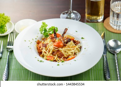 Spaghetti Tasty appetizing classic italian pasta in tomato sauce and pasta sauce, in white dish on table.Plate of Italian spaghetti food is Scallop pesto clam. Bolognese sauce in dish with napkin.