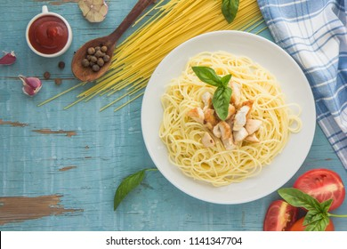 Spaghetti with tomato and basil in plate on wooden board and ingredients for cooking pasta