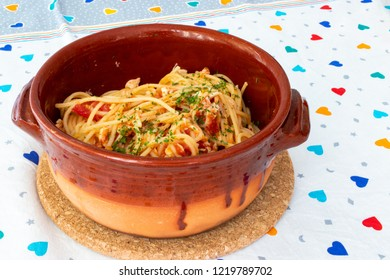 Spaghetti with tomato, basil and sea bass, in earthenware dishes on a colored tablecloth.