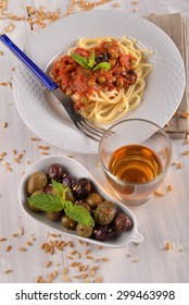spaghetti with tomato and olives and mint leaf