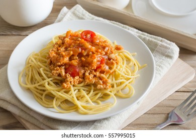 Spaghetti with tomato sauce mix fried egg in white dish on wooden table.