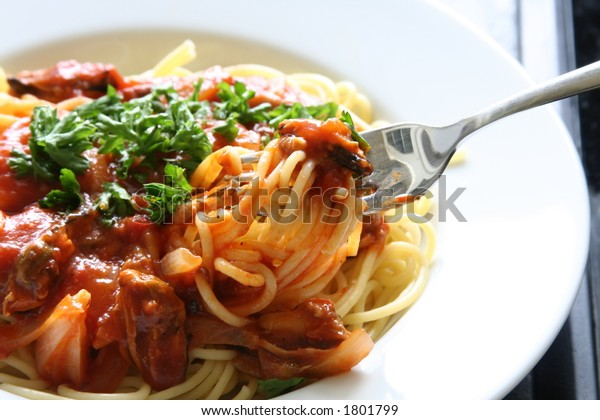 Spaghetti with tomato sauce and persil garnishings (about to taste it using a fork)