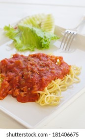 Spaghetti with tomato source on top.