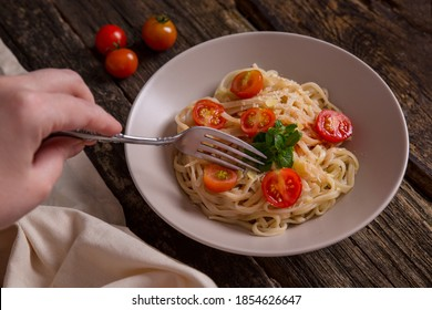 Spaghetti with tomatoes and cheese on a dark wooden table. Hand holds a fork with spaghetti.