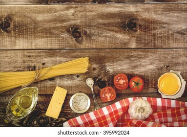 Spaghetti, tomatoes and cheese on a wooden background . Pasta Ingredients.  Top view