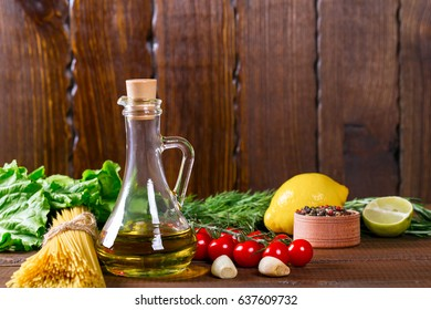 Spaghetti, tomatoes cherry, olive oil, herb and spices on old brown wooden background