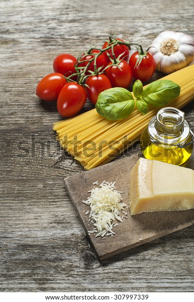 Spaghetti and tomatoes with parmesan cheese on a vintage wooden table