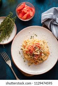 Spaghetti with tomatoes and thyme in a plate on a blue table. Top view.