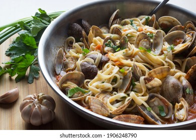 Spaghetti with vongole clams and tomatoes in a frying pan