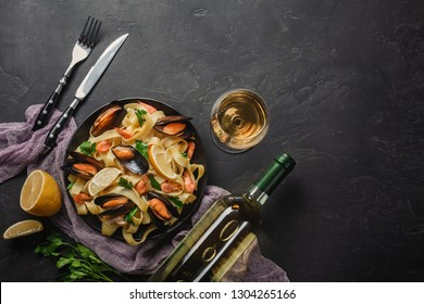 Spaghetti vongole, Italian seafood pasta with clams and mussels, in plate with herbs and glass of white wine on rustic stone background. Traditional Italian sea cuisine, close-up, top view. Copy space