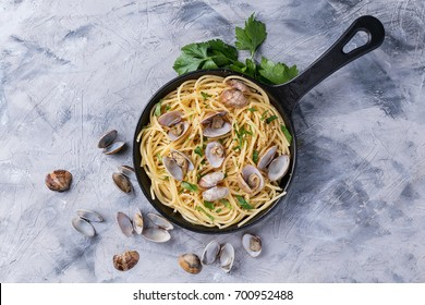 Spaghetti with vongole shellfish decorated with lemon and parsley served on pan over blue background. Top View