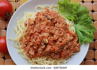 Spaghetti in a white plate and sliced sugar with red ketchup