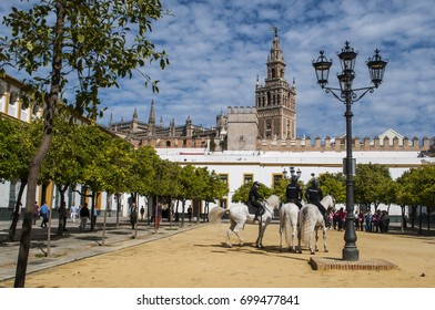 Spain, 18/04/2016: police officers on horseback on the sand in the Patio de Banderas (Courtyard of the Flags) , the starting point of the Jewish Quarter of Seville, with view of the Giralda bell tower