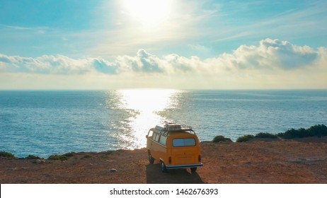 Spain, 2019,june,1, Aerial view. Yellow VW bus van on a parking lot on a rock near the sea.